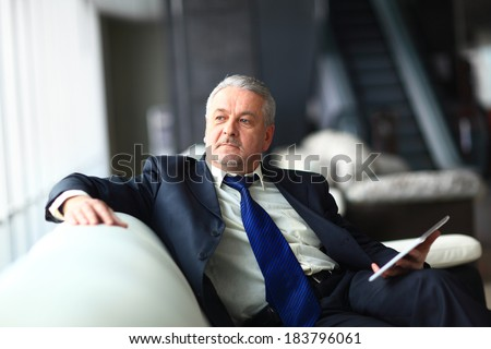 Portrait of a mature businessman with digital tablet - stock photo