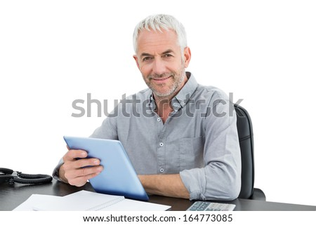 Portrait of a mature businessman with digital tablet and telephone at desk against white background - stock photo