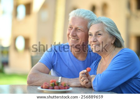 Portrait of a mature couple eating berries on table - stock photo