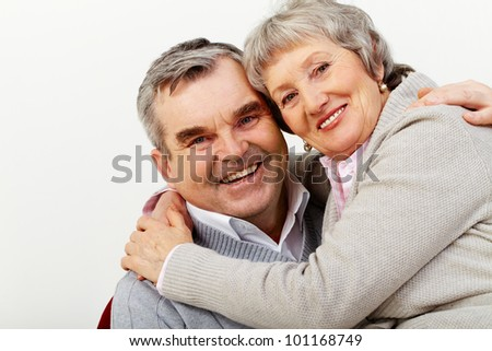 Portrait of a mature couple happily hugging and looking at cam - stock photo