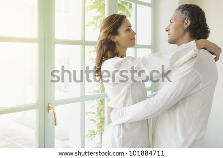 Portrait of a mature couple hugging at home, standing by large garden doors. - stock photo