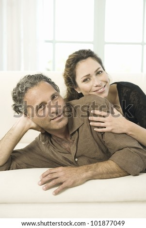 Portrait of a mature couple laying down on a white sofa, smiling at the camera.