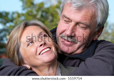 Portrait of a mature couple smiling to each other. - stock photo
