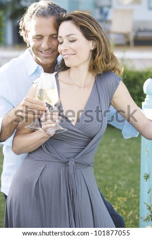 Portrait of a mature couple toasting with champagne while leaning on a hotel's balcony outdoors. - stock photo