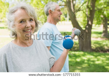 Portrait of a mature couple using dumbbells at the park - stock photo
