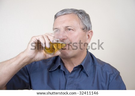 Portrait of a mature gentleman drinking beer from a glass - stock photo