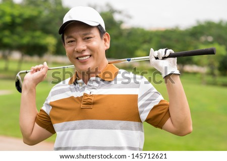 Portrait of a mature golf player smiling and looking at camera - stock photo