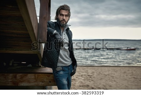Portrait of a mature handsome man resting on the autumn beach - stock photo