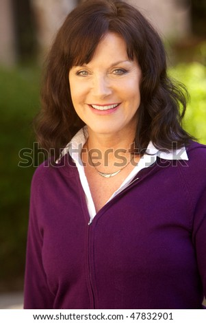 Portrait of a Mature Happy Woman Looking at Camera - stock photo