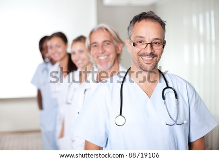 Portrait of a mature male doctor standing in front of his team and smiling