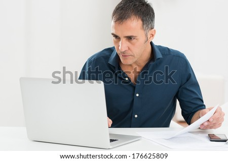 Portrait Of A Mature Man Looking At Laptop Holding Document - stock photo