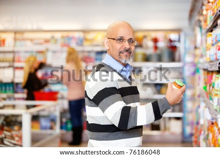 Portrait of a mature man shopping in the supermarket with people in the background - stock photo