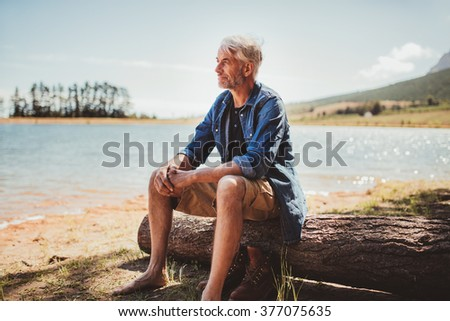 Portrait of a mature man sitting on a log near the lake. Senior caucasian man sitting alone on the lake and looking at a view on a summer day. - stock photo