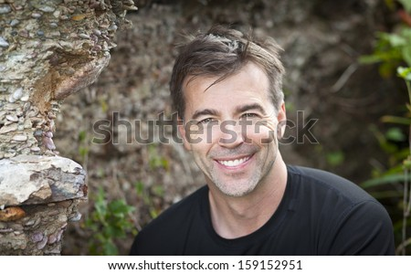 Portrait Of A Mature Man Smiling At The Camera - stock photo