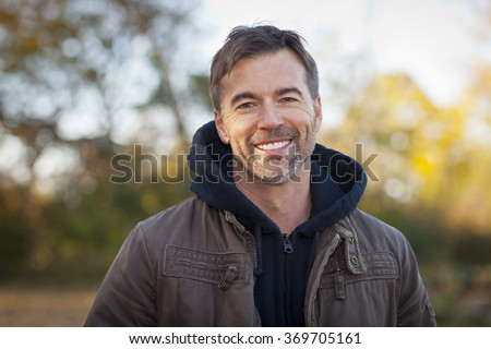 Portrait of A Mature Man Smiling At The Park - stock photo