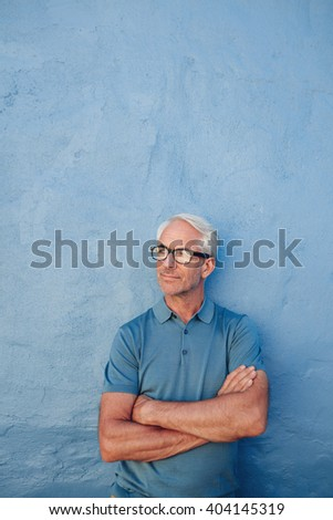 Portrait of a mature man standing with his arms crossed against a blue wall. Caucasian male wearing glasses looking away at copy space. - stock photo