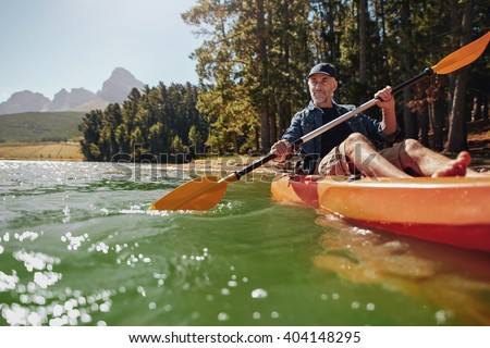Portrait of a mature man with enjoying kayaking in a lake. Caucasian man wearing a cap paddling a kayak on summer day. - stock photo