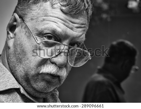 Portrait of a mature mustachioed man in glasses and his reflection in the window - stock photo