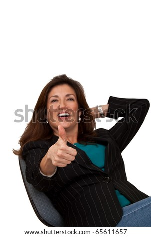 Portrait of a mature pretty businesswoman wearing blue blouse, jeans, and a black jacket.  Isolated on white background. She has extended arm with thumbs up with selective focus on thumb. - stock photo