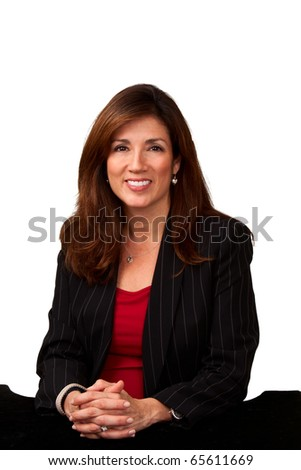 Portrait of a mature pretty businesswoman wearing red blouse and a black jacket and sitting a small black table.  Isolated on white background. - stock photo