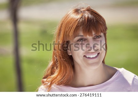 Portrait Of A Mature Red woman smiling and looking away - stock photo