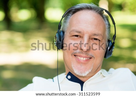 Portrait of a mature smiling man listening music outdoors - stock photo