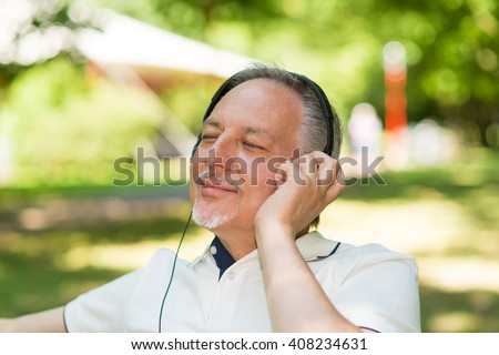Portrait of a mature smiling man listening music outdoors