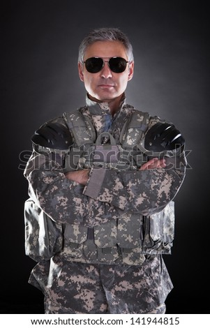 Portrait Of A Mature Soldier Wearing Sunglasses Over Black Background