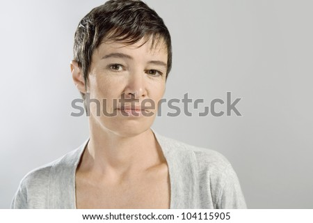 Portrait of a mature woman against a grey background.