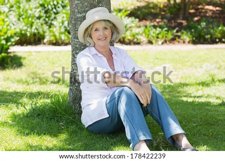 Portrait of a mature woman sitting against a tree in the park - stock photo
