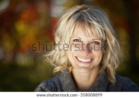 Portrait Of A Mature Woman Smiling And Looking At the Camera - stock photo