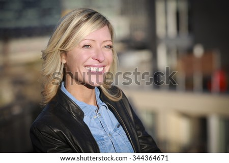 Portrait Of A Mature Woman Smiling At The City - stock photo