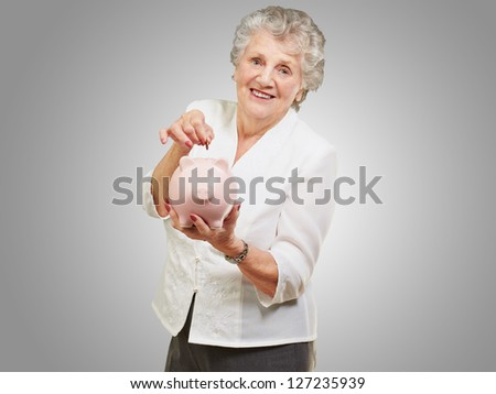 Portrait Of A Mature Woman With A Piggy Bank On Gray Background - stock photo