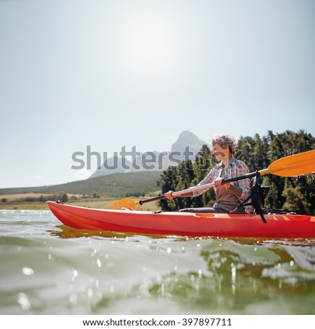 Portrait of a mature woman with kayak in a lake. Senior woman paddling kayak on a summer day. - stock photo