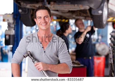 Portrait of a mechanic holding an air powered socket - stock photo
