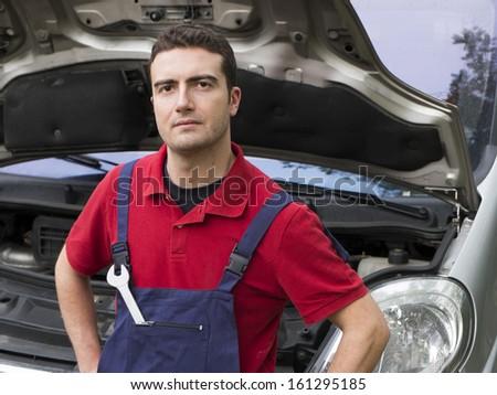 portrait of a mechanic  in auto repair shop - stock photo