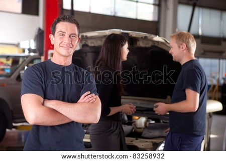 Portrait of a mechanic looking at the camera with a customer and second mechanic in the background - stock photo