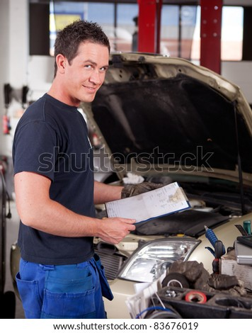 Portrait of a mechanic, looking at the camera with a service report in hand - stock photo