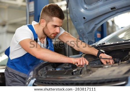 Portrait of a mechanic servicing a car at his workshop