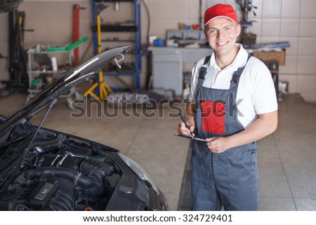 Portrait of a mechanic taking notes and smiling
