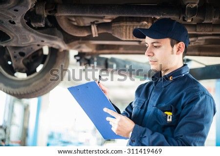 Portrait of a mechanic taking notes under a car - stock photo
