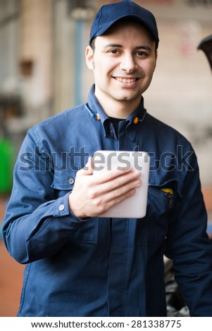 Portrait of a mechanic using a tablet in his garage - stock photo
