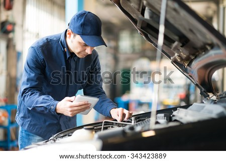 Portrait of a mechanic using a tablet in his garage