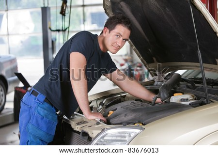 Portrait of a mechanic working on car in garage - stock photo