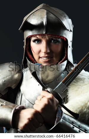Portrait of a medieval female knight in armour over black background. - stock photo