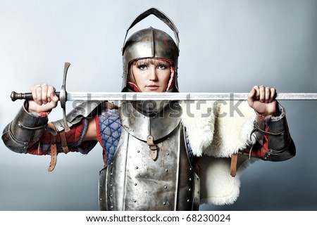 Portrait of a medieval female knight in armour over grey background. - stock photo
