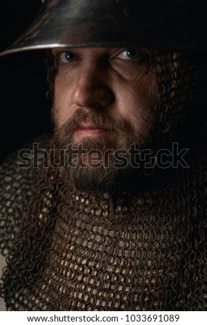 Portrait of a medieval infantry man wearing his elm and chainmail. Historical reenactment portrait in a flemish painting style