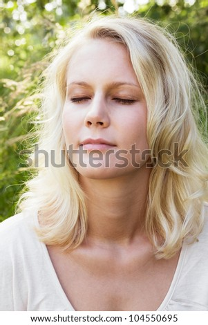 Portrait of a meditating blond woman with closed eyes. Summer outdoor shot against a blurry green background. - stock photo