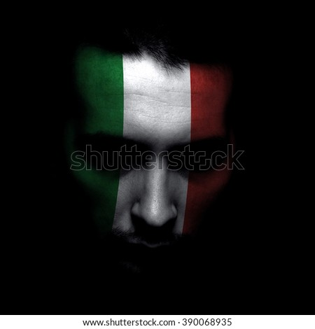 Portrait of a men with the flag of the Italian / Mexican painted on face. - stock photo