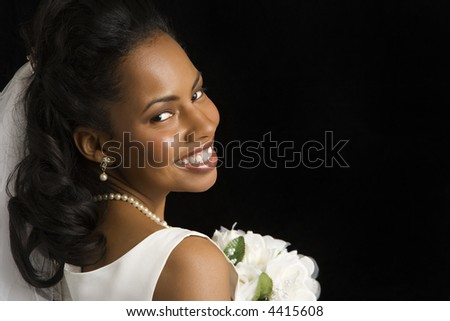 Portrait of a mid-adult African-American bride on black background. - stock photo